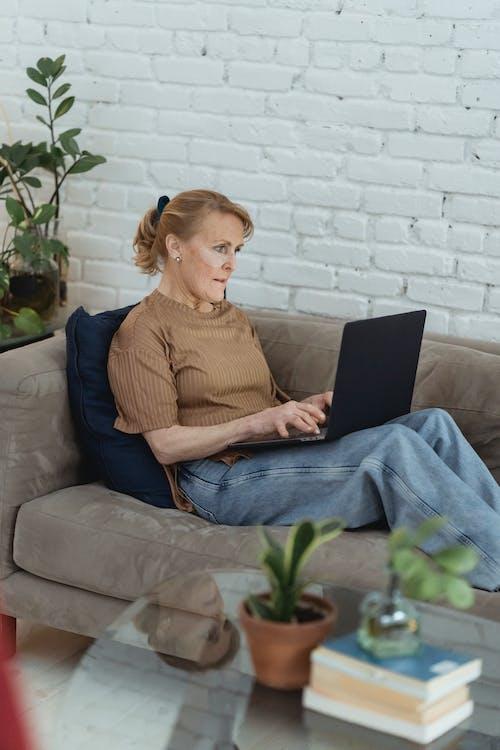 Focused mature woman using laptop on sofa