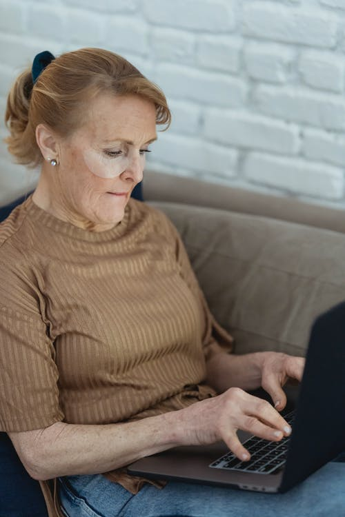 Mature woman in eye patches suing laptop on couch