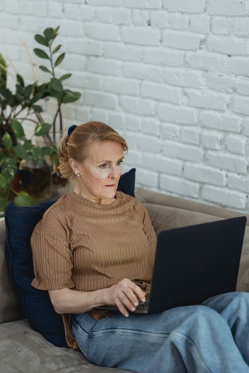Concentrated senior female wearing casual outfit and hydrating eye patches working on modern netbook and lying on cozy sofa in modern living room