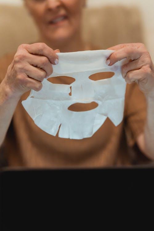 Crop glad mature woman applying moisturizing face mask