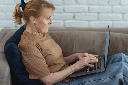 Side view crop concentrated mature female wearing eye patches surfing contemporary netbook on laps while lying on comfy couch at home