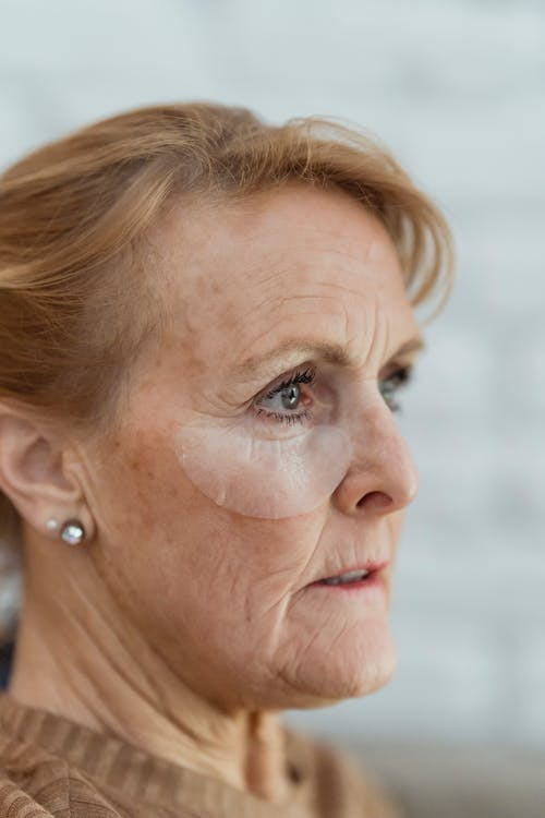 Crop mature woman with eye patches looking away pensively
