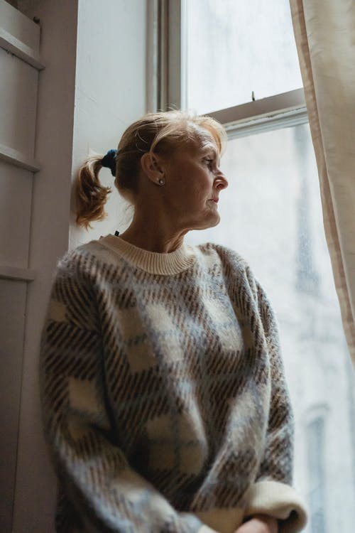Contemplative senior female wearing warm sweater sitting on windowsill and looking out window in contemplation