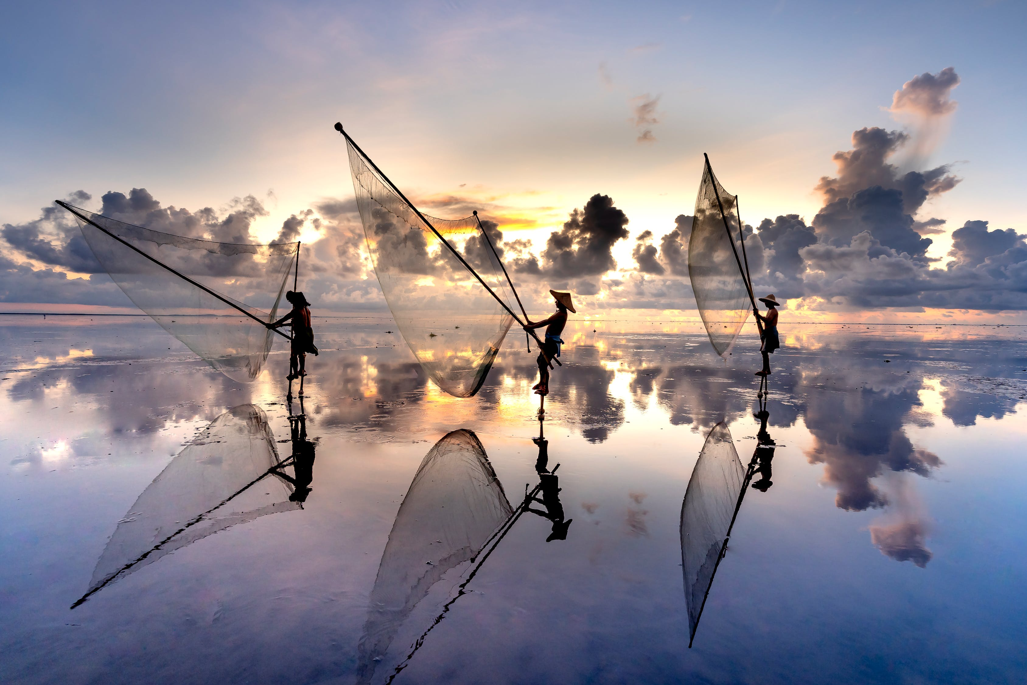 Silhouette of Fishermen with Their Fishnets