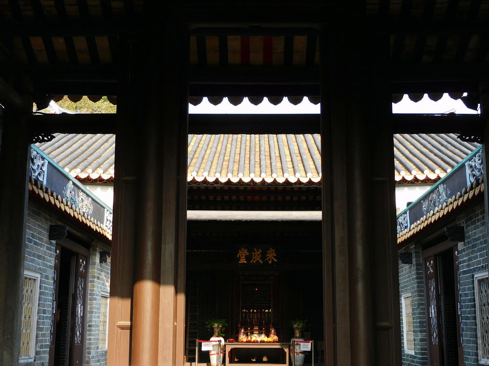 Gate leading to yard of ancient Buddhist shrine on sunny day in Hong Kong