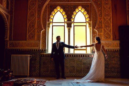 Man in Black Suit Standing Beside Woman in White Wedding Dress
