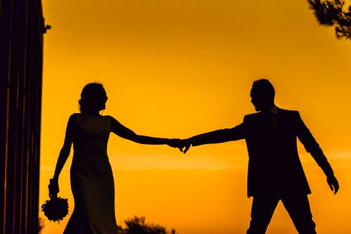 Silhouette of Man and Woman Holding Hands during Sunset