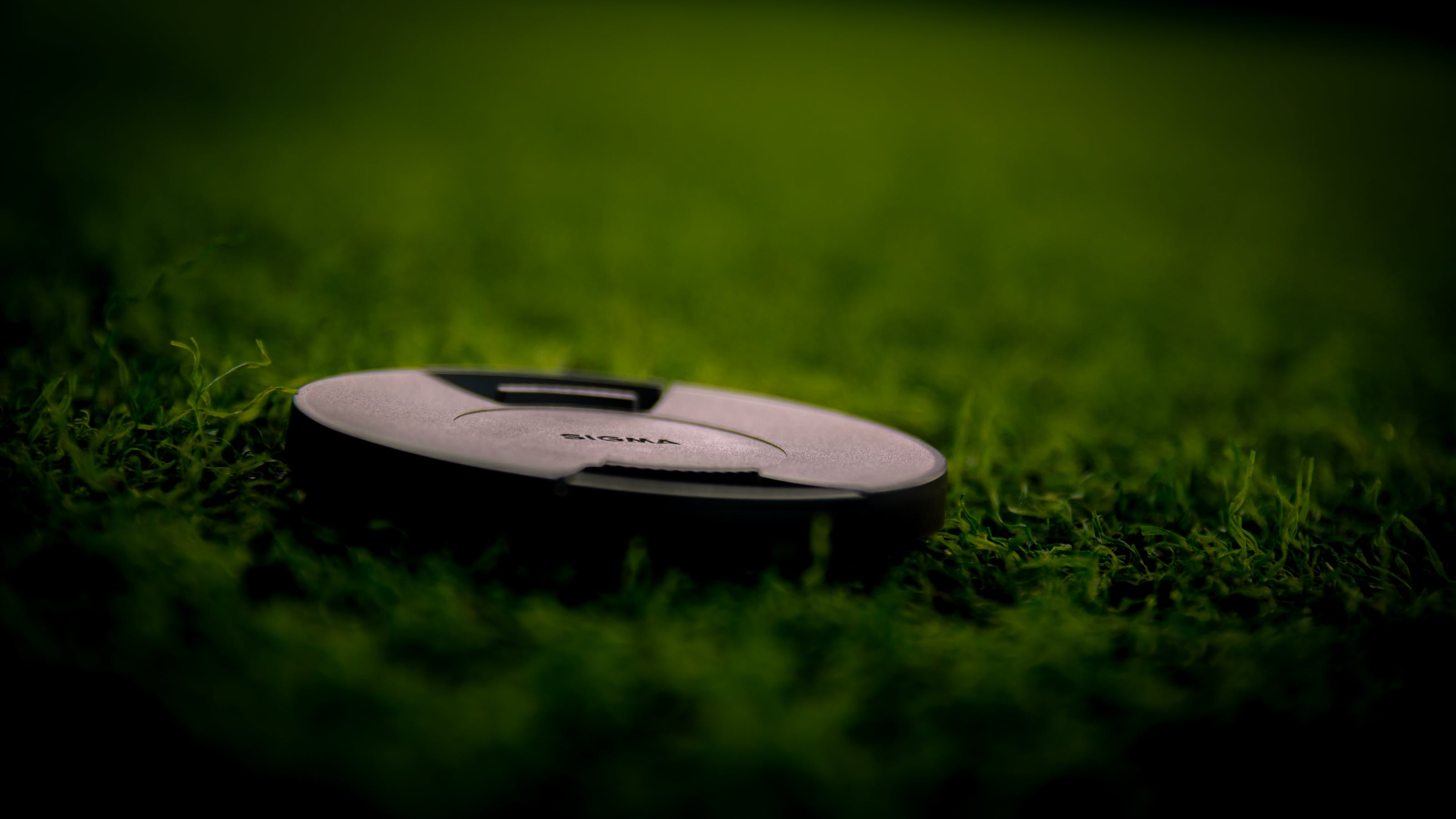 Black Camera Lens Cover on Green Grass