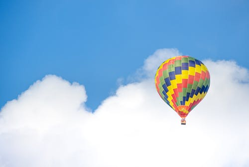 Yellow Blue and Green Hot Air Balloon Flying Near White Clouds