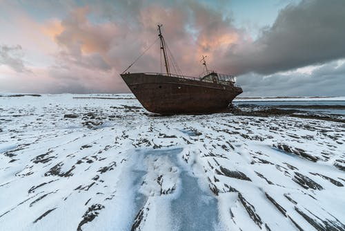 Brown Boat on Snow Covered Ground