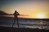 Silhouette of Woman Holding Camera Near Seashore during Golden Hour