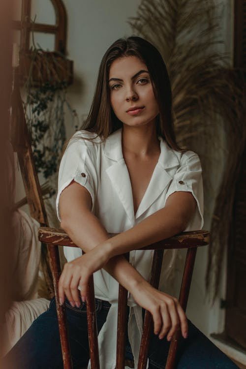 Woman in White Button Up Shirt Sitting on Brown Wooden Chair