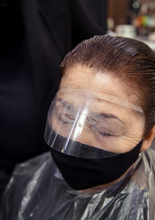 From above of middle aged female with eyes closed in protective mask dying hair in salon