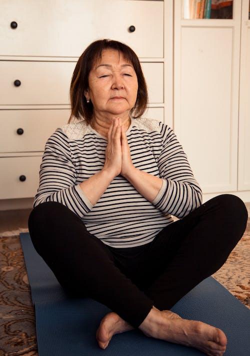 Elderly Asian woman meditating on floor
