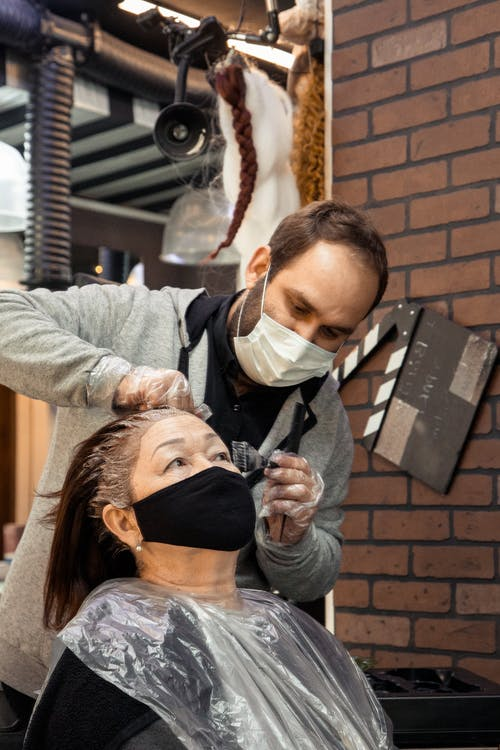 Bearded man in protective mask applying hair die for aged female in modern salon