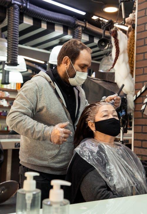 Experienced bearded hairdresser dying hair of senior woman