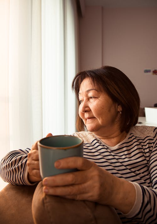 Asian aged woman with cup of coffee resting on sofa