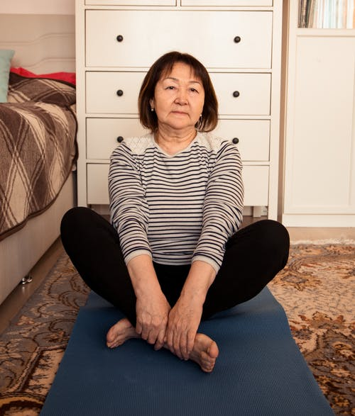 Full body of aged ethnic female with short hair relaxing on rug at home in daytime