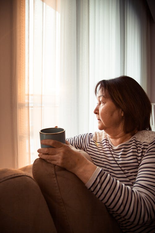 Elderly thoughtful Asian woman with cup of tea in lounge