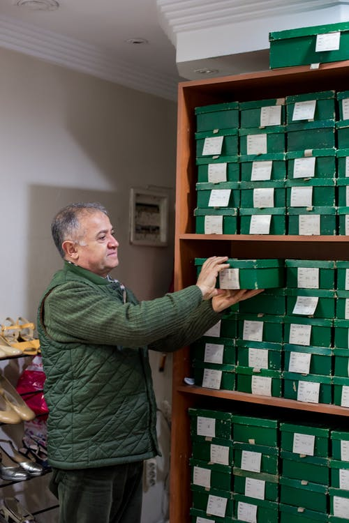 Positive middle aged man in casual outfit putting boxes with shoes on shelves while standing in bright shoe shop near and looking away