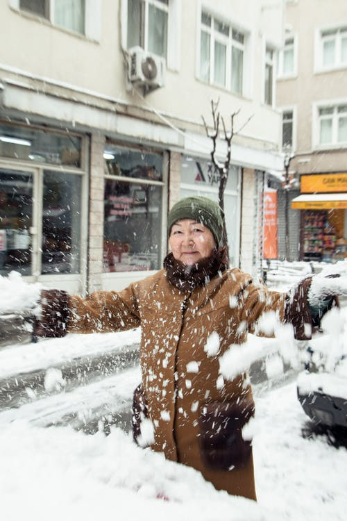 Woman in Brown and White Coat Standing on Snow Covered Ground