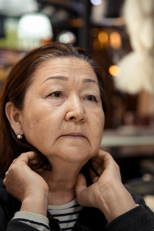 Thoughtful senior Asian woman with in casual clothes adjusting hair and pensively looking away against blurred background