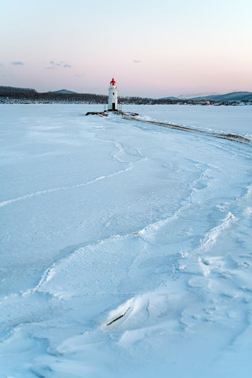 White Lighthouse on Snow Covered Ground
