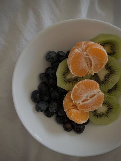 Bowl with mandarins and blueberries with sliced kiwi on bed
