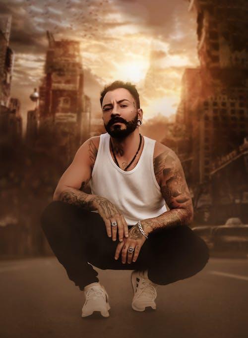 Brutal man squatting down on street at sundown