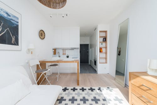 White couch placed on rug near table and drawer in stylish room with mirror and decorated shelves and long corridor with door