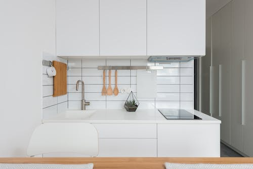 Wooden table placed near white cupboards in modern kitchen with minimalist interior in daylight