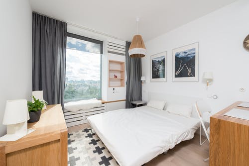 Interior of modern bedroom with comfortable bed with white pillows and sheet and wooden furniture decorated with paintings and curtains