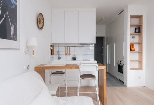 Comfortable sofa placed near wooden counter and kitchen in apartment