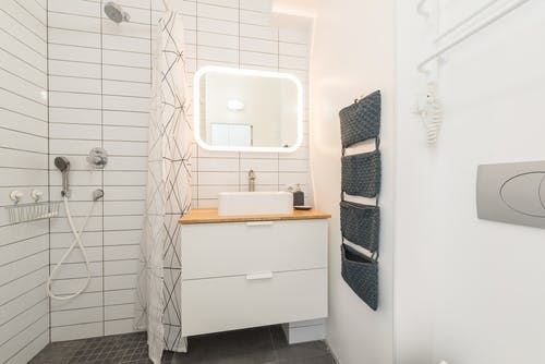 Interior of contemporary bathroom with white furniture and shower cabin near illuminated mirror and ceramic sink