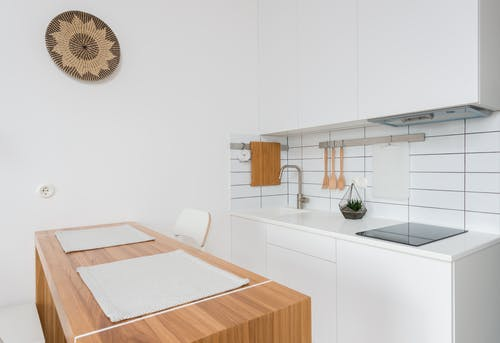 Wooden table with chairs in contemporary kitchen with white cabinets and modern appliances in daylight