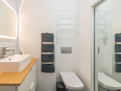 Small modern bathroom with ceramic toilet bowl and sink under illuminated mirror in modern apartment