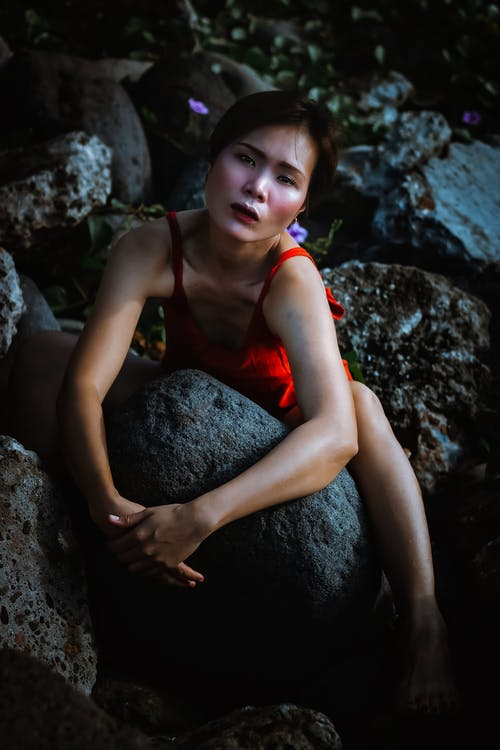 Serious young Asian lady in red dress on rocky stones looking at camera in daytime