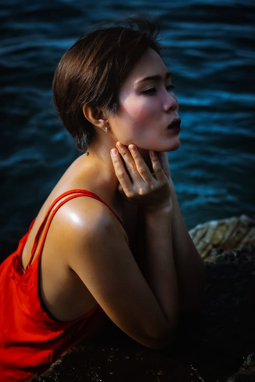 Side view of thoughtful young ethnic woman in red dress leaning on stone near water while looking away in daylight