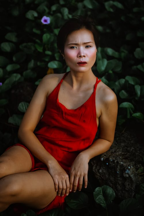 Woman in Red Tank Top Sitting on Rock