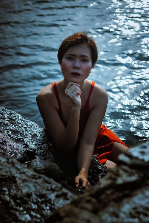 Woman in Orange Dress Sitting on Rock Near Body of Water