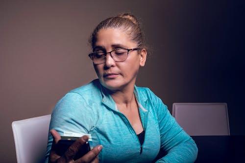 Immagine gratuita di donna, donna che guarda il suo telefono, latino