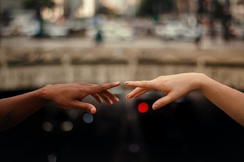 Diverse couple touching hands on street