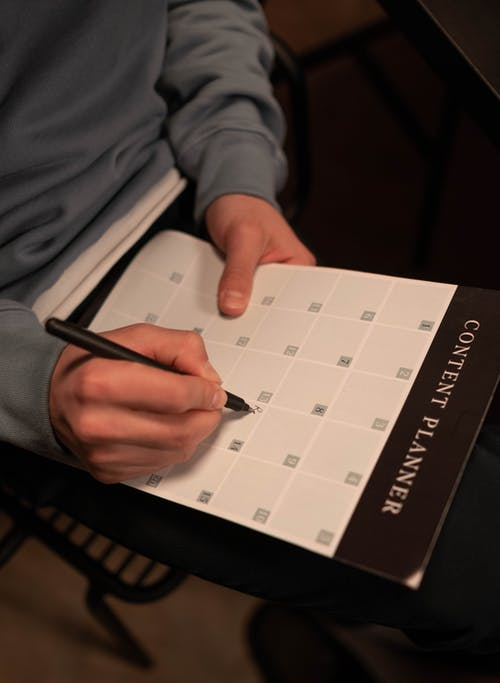 Person Writing on a Calendar Planner