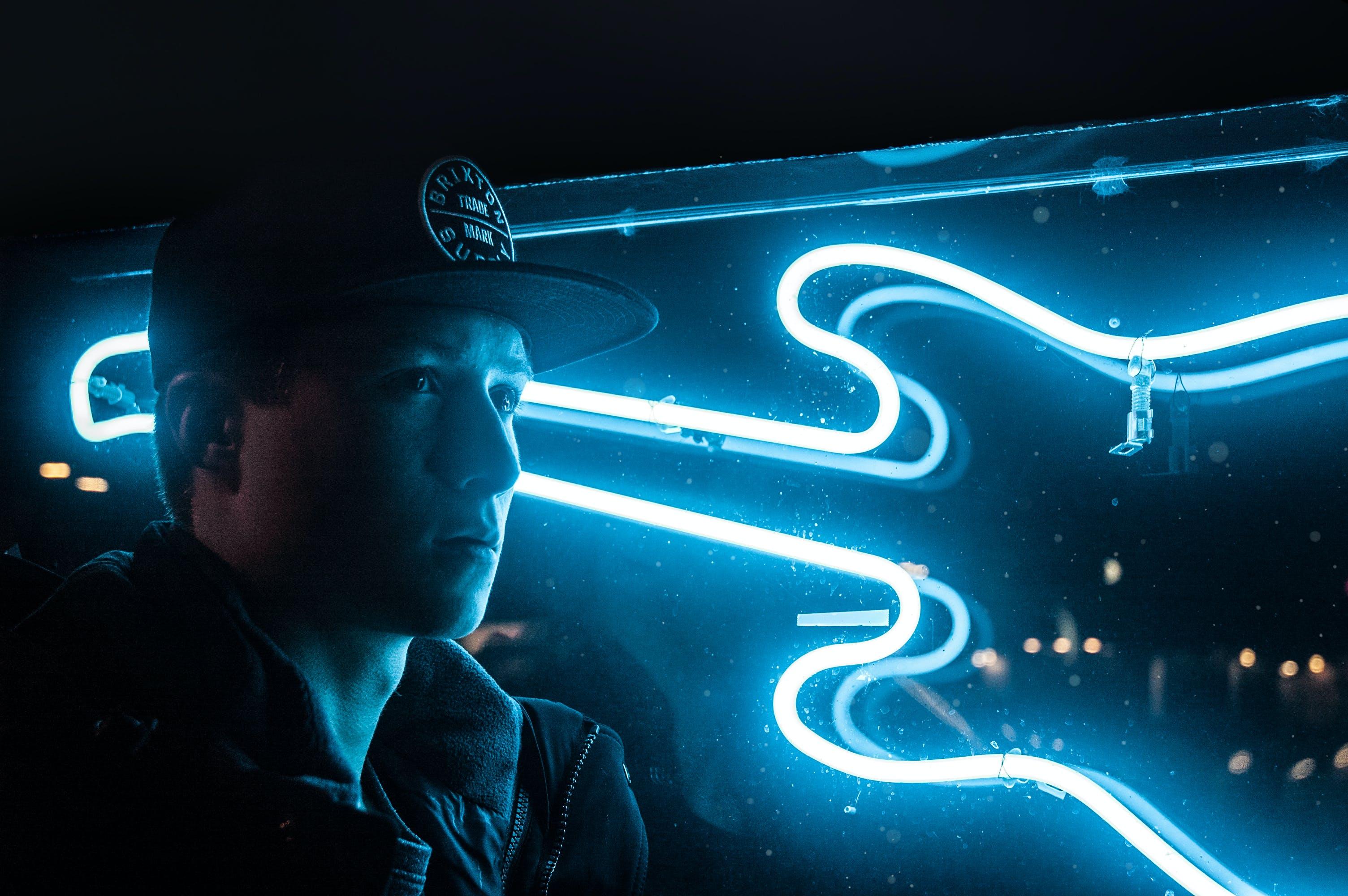Man In Black Jacket Beside Blue Neon Light Guitar