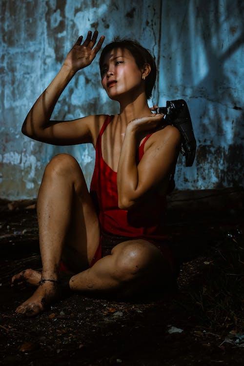 Woman in Red Tank Top Sitting on Black Rock