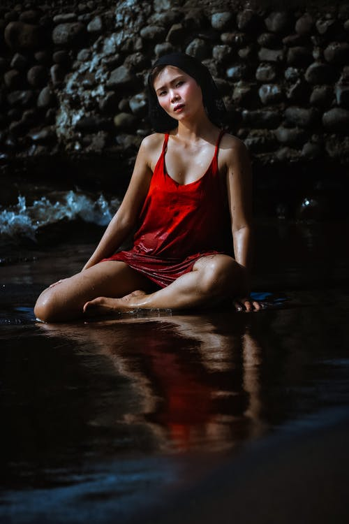Woman in Red Tank Top Sitting on Water