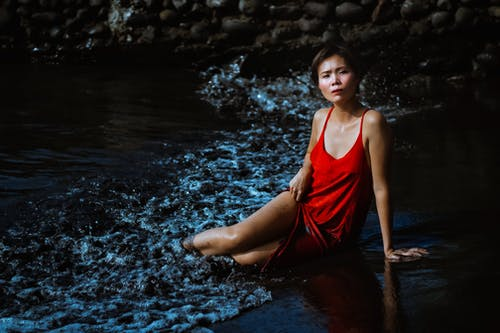 Woman in Red One Piece Swimsuit Sitting on Water