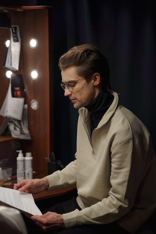 Man in Gray Jacket Holding A Script