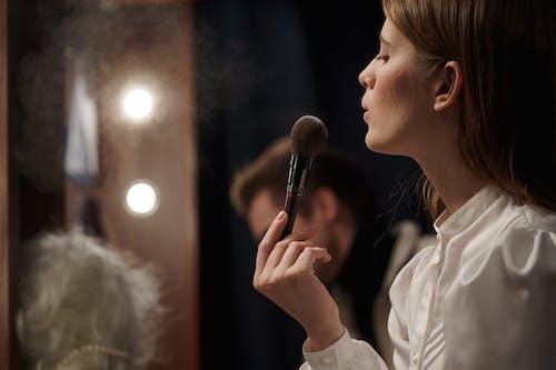 Woman in White Shirt Holding Makeup Brush
