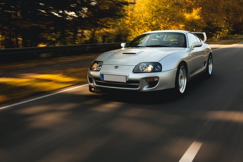 Man Driving A Silver Toyota Supra on Road